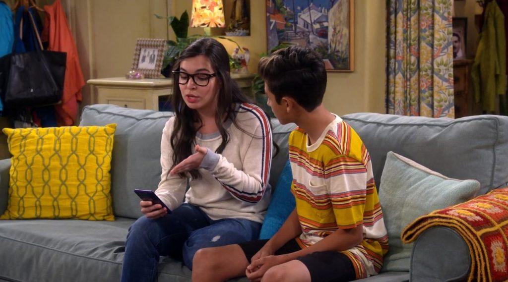 Elena und Alex sitzen auf der Couch und Elena zeigt ihm etwas auf dem Handy mit erklärender Geste.
