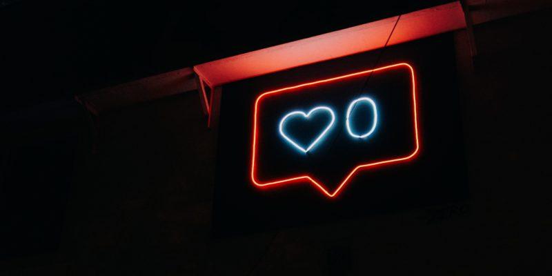 """Eine Leuchtreklame in Form des """"Like""""-Symbols auf Instagram illuminiert die ansonsten nicht identifizierbare Umgebung in weiß und rot. Es sind bisher 0 Likes gezählt."""
