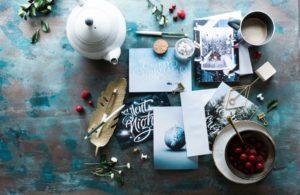 Ein Flatlay von einem Tisch mit Bastelkram, einer Feder, einer Teekanne und Briefpapier