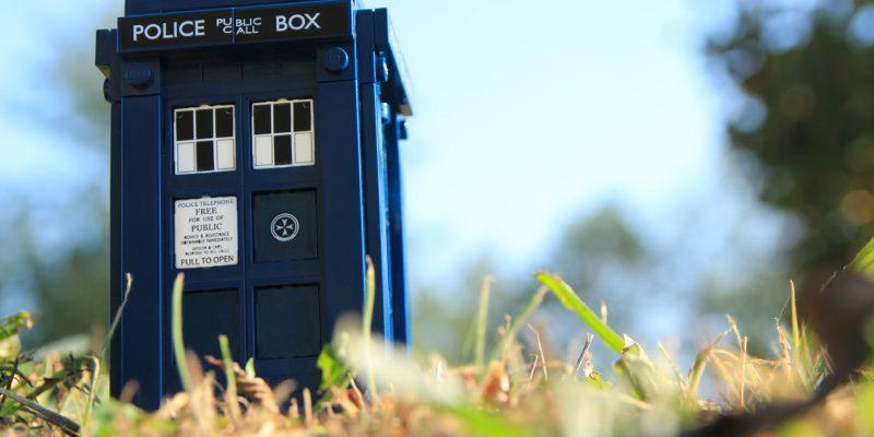 Eine typisch britische blaue Police Box steht auf einer Wiese. Es handelt sich aber um eine Miniaturversion.