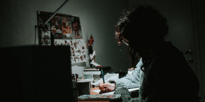 Eine Person sitzt aufgrund von Corona zu Hause am nur von einer Schreibtischlampe belichteten, vollen Schreibtisch und versucht, einen Überblick über das Chaos zu gewinnen.