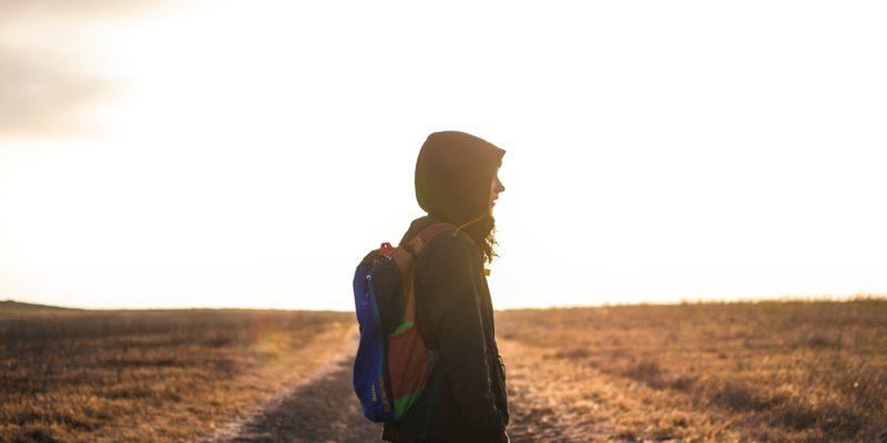 Frau steht alleine auf einer Straße, rechts und links Feld, die Sonne geht gerade unter
