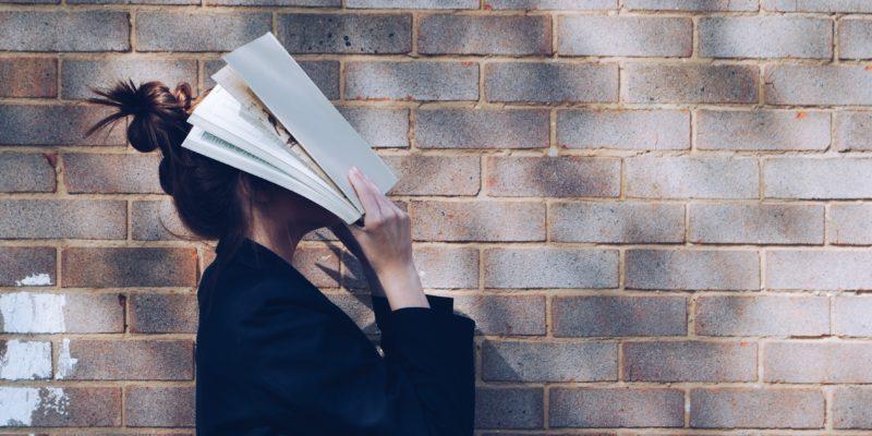Eine Frau vor einer Steinmauer, sie verbirgt ihr Gesicht hinter einem offenen Buch