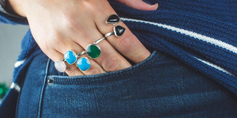 Eine weiße Hand mit mehreren Ringen und schwarzem Nagellack auf dem Daumen. Die andernen Finger sind teilweise in einer engen Hosentasche. Der kleine Finker und Ringfinger bis zum zweiten Glied, der Mittelfinger etwas weniger, der Zeigefinger lediglich bis zum ersten Glied.